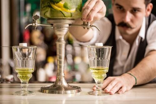 這款是苦艾酒,在文學作品中,苦艾酒常被稱作「綠精靈(la fée verte)」。製法會是這樣的:先以冰水滴進方糖方塊中,繼而再慢慢滲滴融入至苦艾酒內。為了使苦艾酒的味道更層次分明,餐廳在滴漏過程中加入自家製浸泡各款蔬果或香草的冰水,如青瓜、檸檬配薄荷、茉莉配青蘋果或是香橙配迷迭香等,每日以不同口味的浸泡水調製苦艾酒,餐廳同時供應一系列以苦艾酒調製的雞尾酒,包括Strangled Parrot,Burlesque 及Trinité等。